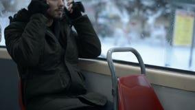 Sluit de portret omhoog Jonge langharige gebaarde mens in een jasje en de grote hoofdtelefoons zit langs in openbaar vervoer door stock videobeelden
