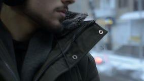 Sluit de portret omhoog Jonge langharige gebaarde mens in een jasje en de grote hoofdtelefoons zit langs in openbaar vervoer door stock footage