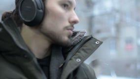 Sluit de portret omhoog Jonge langharige gebaarde mens in een jasje en de grote hoofdtelefoons zit langs in openbaar vervoer door stock video