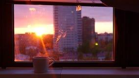 Sluit de zonneblinden op het venster met een mooie avondzonsondergang, en een kop van ruwe koffie met stoom op de vensterbank stock video