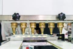 Sluit deeg of room en pijp omhoog lossing die van automatische koekje of snoepjes machine in productielijn voor geavanceerd techn royalty-vrije stock afbeelding