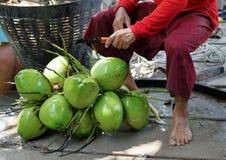Sluit een mens uitwerkt kokosnoot door mes royalty-vrije stock fotografie