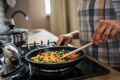 Sluit en snijd omhoog mening van de handen die van de vrouw pan houden en voedsel daar mengen in Zij bevindt zich in keuken bij f stock fotografie