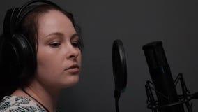 Sluit extra van romantisch jong meisje zingt omhoog lied Sluit omhoog van meisje in hoofdtelefoons in vocale studio stock video