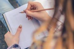 Sluit foto van meisje ` s overhandigt het schrijven omhoog samenstelling in haar agenda stock fotografie