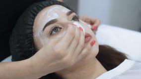 Sluit gezicht van mooi meisje doet omhoog kosmetische procedure in schoonheidssalon, langzame motie stock video