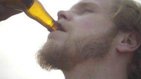 Sluit gezichts omhoog aantrekkelijk gebaard mens het drinken bier en in openlucht het genieten van van drank De kerel proeft lage stock video