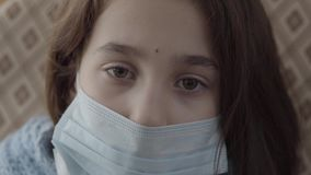 Sluit gezichts omhoog droevig ziek meisje die met een steriel masker op haar gezicht de camera dicht omhoog onderzoeken Het meisj stock video