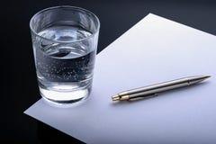 Sluit glaswater, omhoog pen en document blad donkere achtergrond stock afbeeldingen