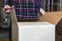 Sluit hand omhoog open doos met dingen wanneer zich het bewegen aan het nieuwe huishuis F stock foto's
