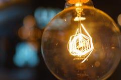 Sluit innovatie omhoog verlichte gloeilamp met bokehs zoals creëren stock afbeeldingen