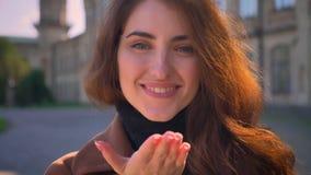 Sluit Kaukasisch brunette verzendt omhoog slagkus en bekijkt camera met gelukkig gezicht, mooie illustratie in stedelijk stock videobeelden