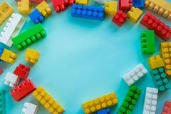 Sluit Kinderen omhoog plastic aannemer op een blauwe achtergrondstreepachtergrond Het ontwikkelen van speelgoed stock fotografie