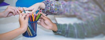 Sluit kleine kinderenhanden opnemen omhoog kleurenpotloden stock foto's