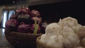 Sluit mening die van ontsproten purper ui en knoflook in rieten mand op de lijst in restaurantkeuken omhoog liggen Camera stock videobeelden