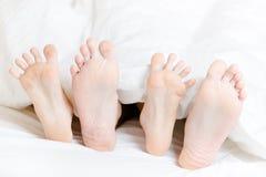 Sluit mening die van voeten van het paar in slaapkamer omhoog liggen Stock Afbeeldingen