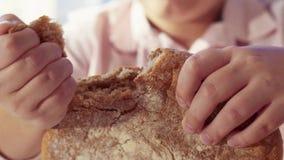 Sluit mening van jonge man's overhandigt omhoog brekend broodbrood bij lijst Keuken, douane en tradities gastvrijheid stock videobeelden
