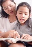Sluit moeder en dochter die een omhoog boek samen lezen stock afbeeldingen