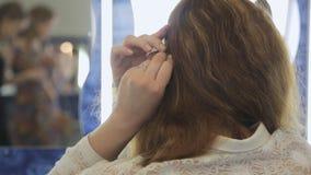 Sluit omhoog achtermening van wijfje die haar in modelschool maken stock videobeelden