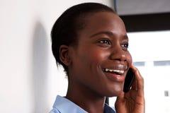 Sluit omhoog Afrikaanse Amerikaanse dame die bij cel telefoon en het glimlachen spreken Royalty-vrije Stock Foto