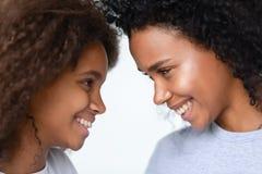 Sluit omhoog Afrikaanse Amerikaanse moeder en tienerdochter die van ogenblik genieten royalty-vrije stock fotografie