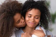 Sluit omhoog Afrikaanse Amerikaanse tienerdochter omhelzend glimlachende moeder stock foto's