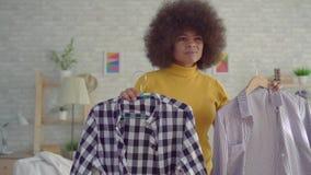 Sluit omhoog Afrikaanse vrouw met een afrokapsel die op kleren voor een spiegel in zijn moderne flat proberen stock videobeelden