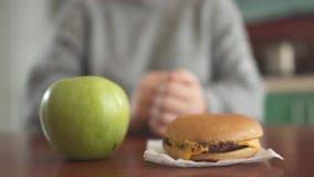 Sluit omhoog appel en hamburger liggend voor vaag cijfer van onherkenbaar mollig meisje De hand van vrouw wil nemen stock footage
