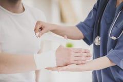 Sluit omhoog Arts Comforting Hand Inury van Patiënt stock foto's