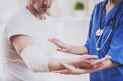 Sluit omhoog Arts Comforting Hand Inury van Patiënt stock afbeeldingen