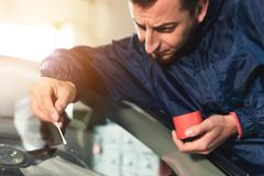 Sluit omhoog Automobiele het bevestigen en de reparatievoorruit van de glazenmakerarbeider of windscherm van een auto in autobenz royalty-vrije stock fotografie