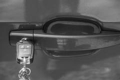 Sluit omhoog autosleutels verlaten in een deur stock afbeelding