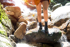 Sluit omhoog Aziatische de vrouwengang van de beenwandelaar een manier in de waterdaling, achtergrondbos royalty-vrije stock foto