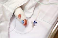 Sluit omhoog babyhand op het bed van de pati?nt in het ziekenhuis met zoute intraveneus Baby bij het ziekenhuis wordt toegelaten  royalty-vrije stock afbeeldingen