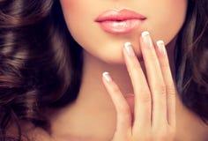 Sluit omhoog beeld van de vingers en de lippen van de vrouw royalty-vrije stock afbeelding