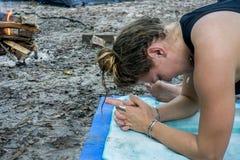 Sluit omhoog beeld van een jonge hippievrouw het praktizeren yoga met veelvoudige zilveren armbanden en ringen in een brandkamp stock fotografie