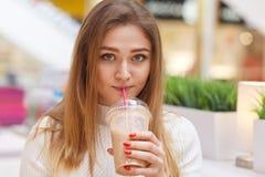Sluit omhoog beeld van gelukkig jong bondewijfje die camera bekijken, zit in koffie en het drinken cocktail, gekleed toevallig wi stock foto