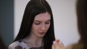 Sluit omhoog beeld van jonge vrouwelijke zitting in modelschool stock videobeelden