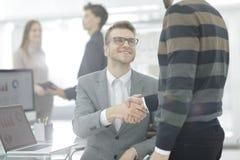 Sluit omhoog beeld van partnershanddruk over bureau tijdens vergadering stock foto