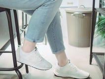 Sluit omhoog been van Aziatisch meisje met jeans en witte sportschoen stock foto