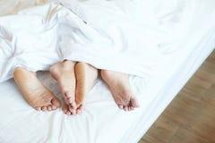 Sluit omhoog benenvoeten de slaap die van het twee Minnaarspaar zij aan zij in het kader van algemene witte bladen in bed thuis o royalty-vrije stock fotografie