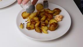 Sluit omhoog Bestrooi de gebraden aardappels met zout Het concept van het voedsel stock video