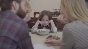Sluit omhoog bezige moeder en vader die aan de keuken bij de lijst met hun ruggen aan camera werken Weinig ongelukkig meisje stock videobeelden