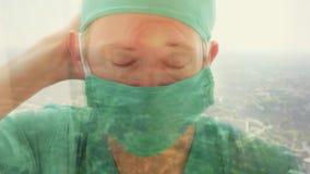 Sluit omhoog bezinning van een arts die uit een venster kijken stock footage