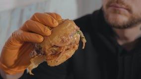 Sluit omhoog blijft van de hamburger ter beschikking hangry jonge man Stock Afbeeldingen
