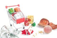 Sluit omhoog boodschappenwagentje met giftdozen, ornamenten en decoratie op wit worden geïsoleerd dat Royalty-vrije Stock Foto