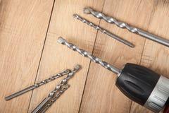 Sluit omhoog boringsmachine, schroevedraaier met boren op houten lijst Voorbereidingen getroffen voor het boren van gaten in beto Royalty-vrije Stock Afbeeldingen