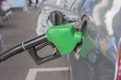Sluit omhoog brandstofpijp. en auto bij benzinestation Royalty-vrije Stock Foto