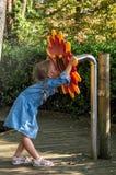 Sluit omhoog Charmant meisje in een blauwe kleding die in het gat van de bloemtelefoon gillen zoals een telefoon van het tinblik royalty-vrije stock fotografie
