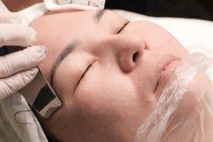 Sluit omhoog De Aziatische vrouw op middelbare leeftijd ligt in het medische bureau van een schoonheidssalon Kosmetische procedur stock afbeelding